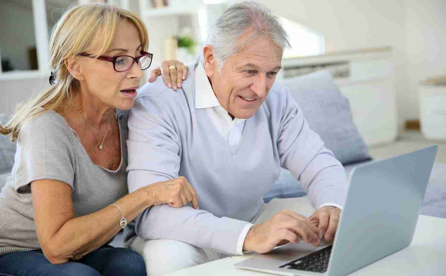 Senior couple confused on laptop needs tech support stock picture